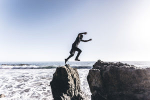 A person leaps from one rock to another in the intertidal zone of a sandy beach.