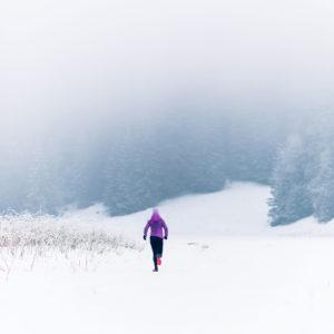 A woman runs across the snow-covered field toward the foggy forest.